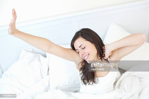 Smiling woman stretching in bed