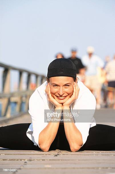 Smiling woman stretching on boardwalk