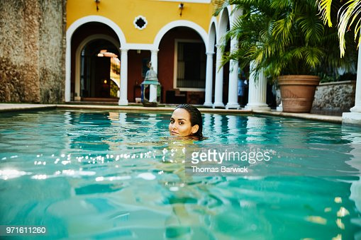 Smiling woman swimming in pool in outdoor spa