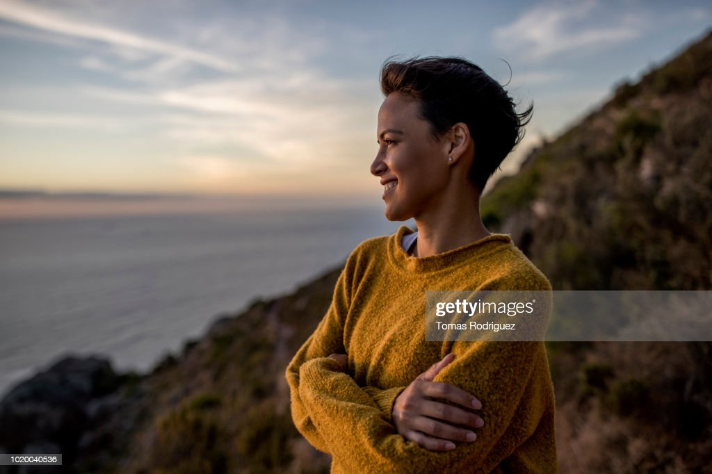 Smiling woman taking a break on a hiking trip looking at view at sunset : Stock-Foto