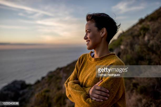 smiling woman taking a break on a hiking trip looking at view at sunset - mid adult women stock pictures, royalty-free photos & images