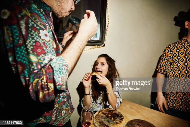 Smiling woman taking bite of pizza during party with friends in night club