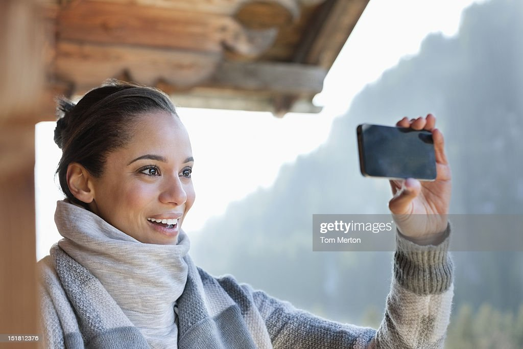 Smiling woman taking photograph with camera phone : Stock Photo