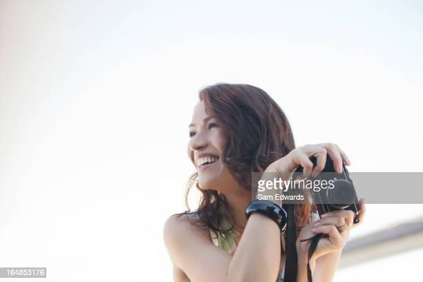 Lächelnde Frau nimmt Fotos im Freien