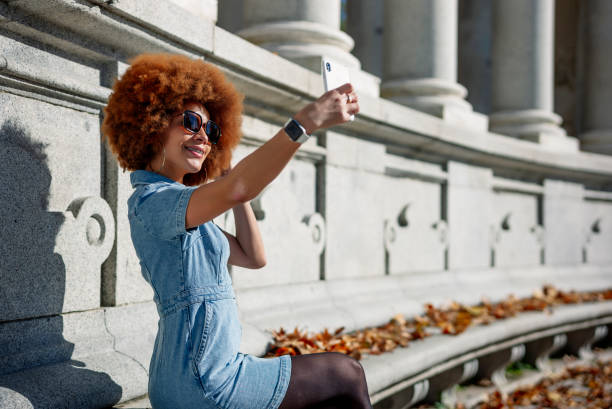 Smiling woman taking selfie at Alfonso Xii Monument on sunny day, Parque Del Buen Retiro, Spain