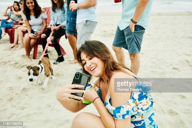 smiling woman taking selfie during beach party with friends - pet equipment stock pictures, royalty-free photos & images