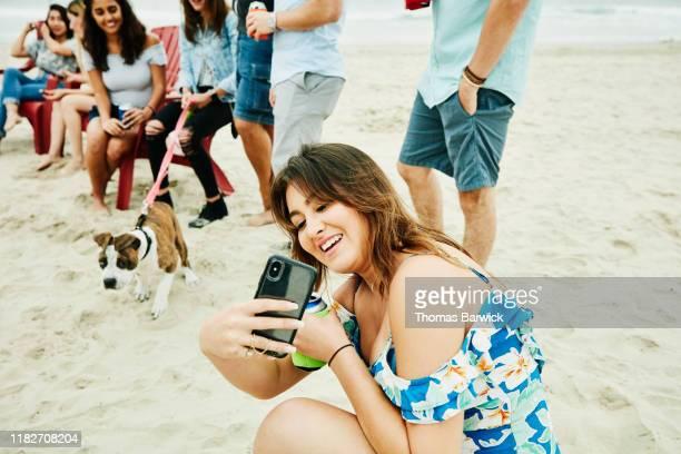 smiling woman taking selfie during beach party with friends - grupo mediano de animales - fotografias e filmes do acervo