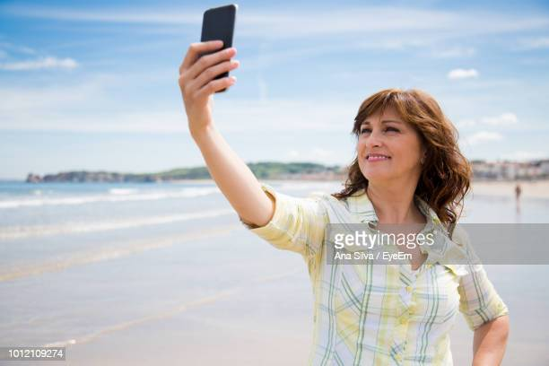 Smiling Woman Taking Selfie On Mobile Phone At Beach