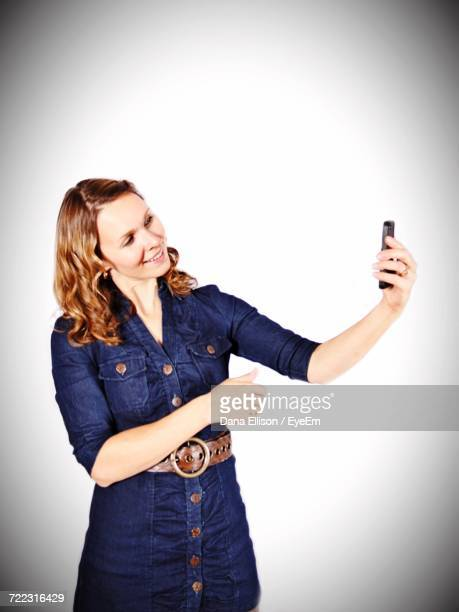 smiling woman taking selfie through smart phone while standing against white background - dana white stock pictures, royalty-free photos & images