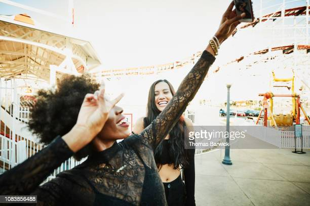 smiling woman taking selfie with smart phone while at amusement park with friends - influencer stock pictures, royalty-free photos & images
