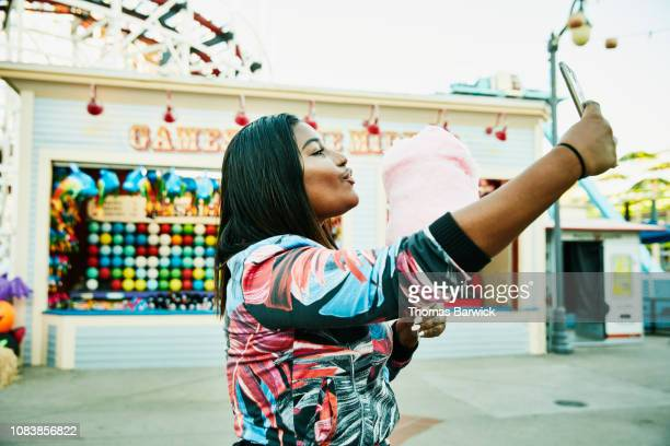 smiling woman taking selfie with smart phone while holding cotton candy during visit to amusement park - influencer stock pictures, royalty-free photos & images