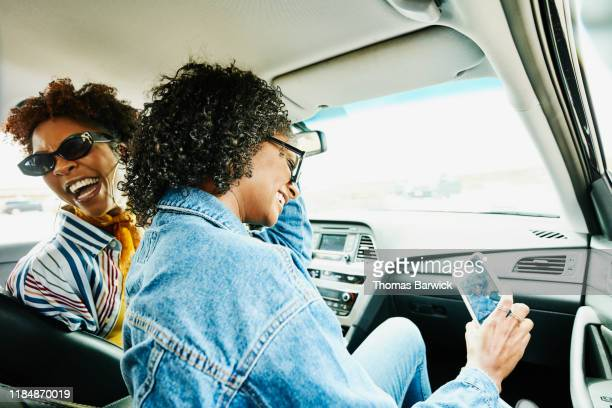 smiling woman taking selfie with smart phone while sitting in passenger seat of car during road trip with friends - landvoertuig stockfoto's en -beelden