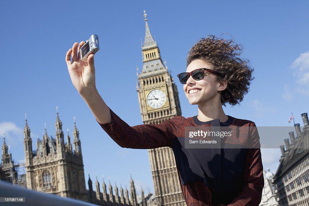 Smiling woman taking self-portrait with digital camera below Big Ben clocktower : Stock Photo