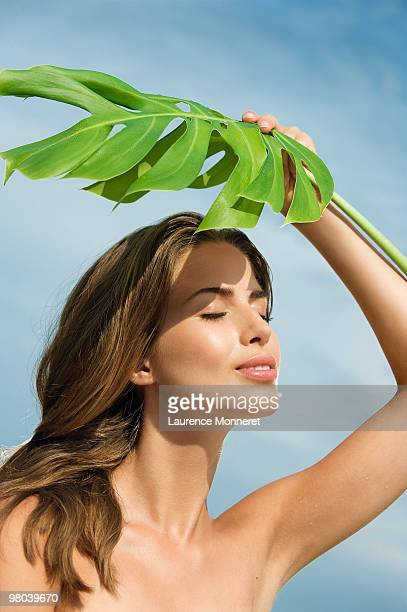 Smiling woman taking sun under a large leaf