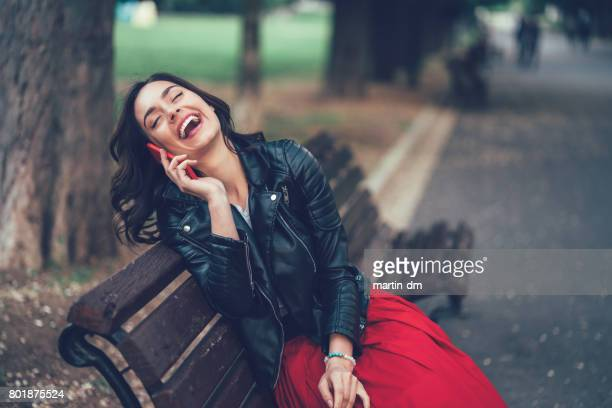 smiling woman talking by the phone - leather skirt stock pictures, royalty-free photos & images