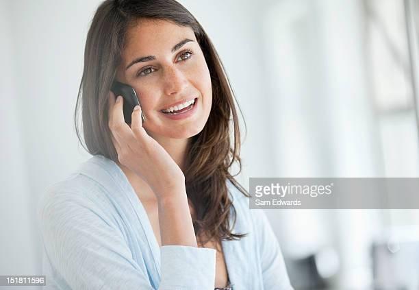 Mujer sonriente hablando por teléfono celular
