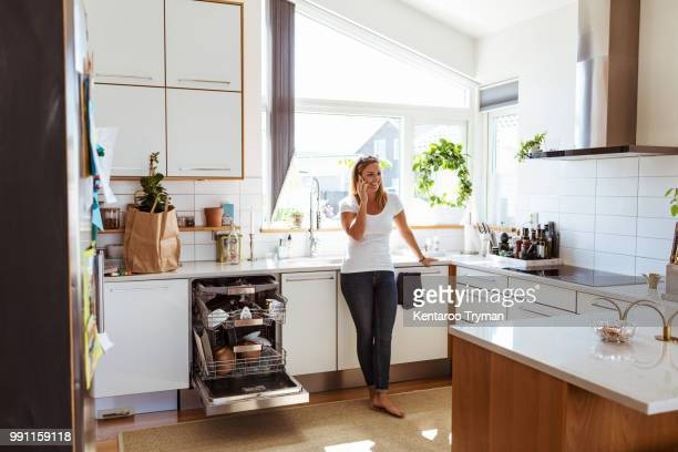 Smiling woman talking on mobile phone while standing in kitchen