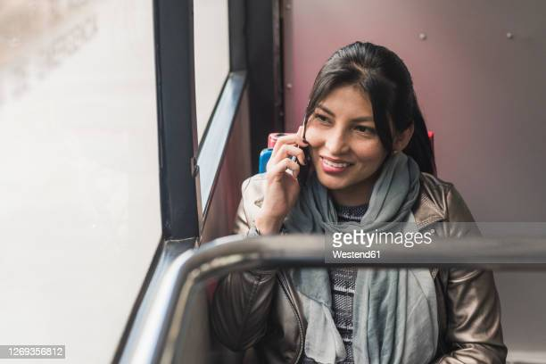 smiling woman talking on mobile phone while traveling in bus - ecuador fotografías e imágenes de stock