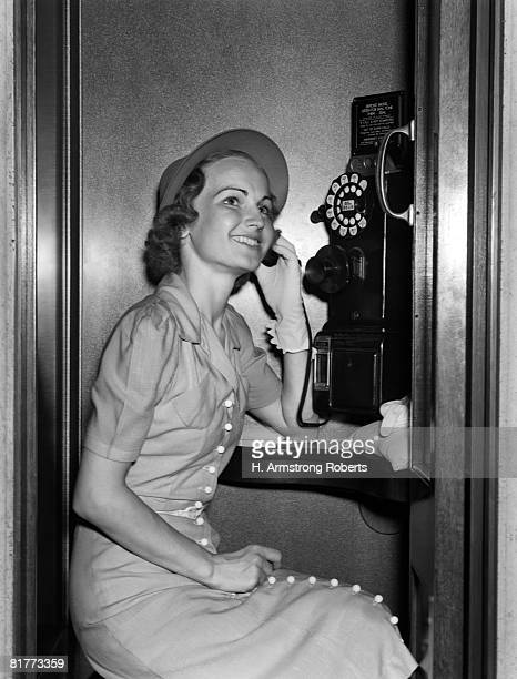 Smiling Woman Talking On Public Dial Coin Pay Telephone In Phone Booth.