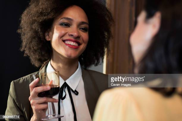 Smiling woman talking to friend while having wine at home