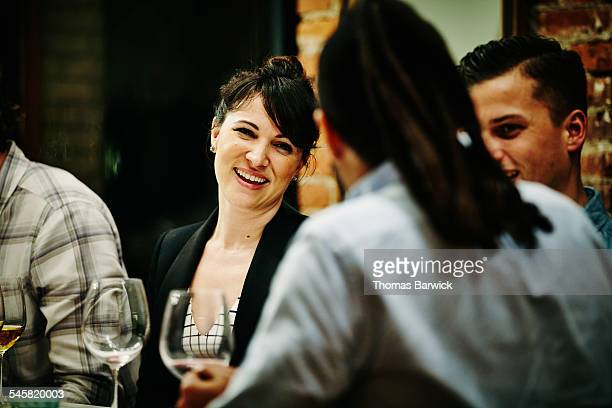 smiling woman talking with friends during dinner - formal stock pictures, royalty-free photos & images