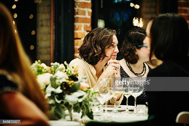 Smiling woman talking with friends during dinner