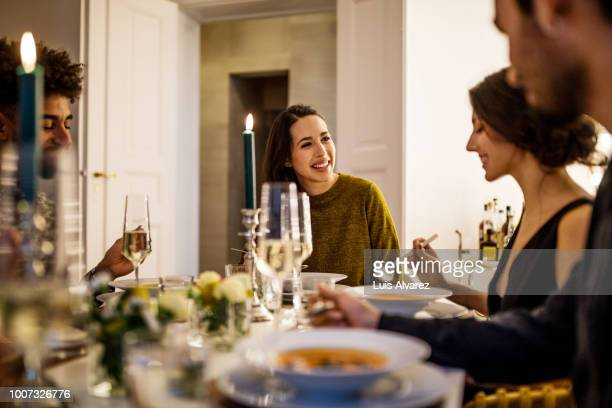 smiling woman talking with friends while having dinner - dinner party stock pictures, royalty-free photos & images