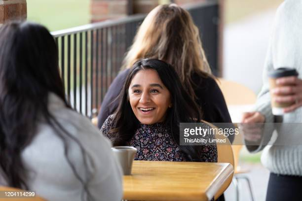 smiling woman talking with her friend in cafe - mid adult women stock pictures, royalty-free photos & images