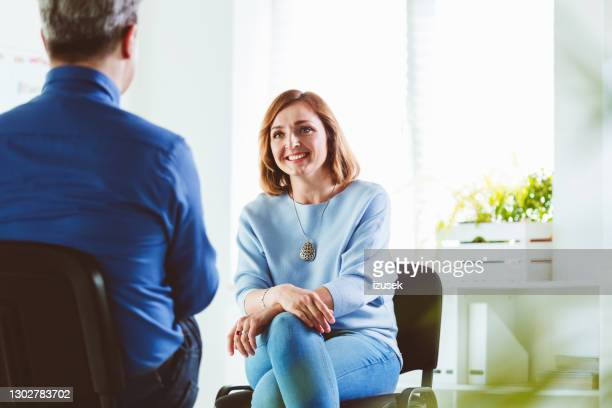 smiling woman talking with psychotherapist - patient stock pictures, royalty-free photos & images