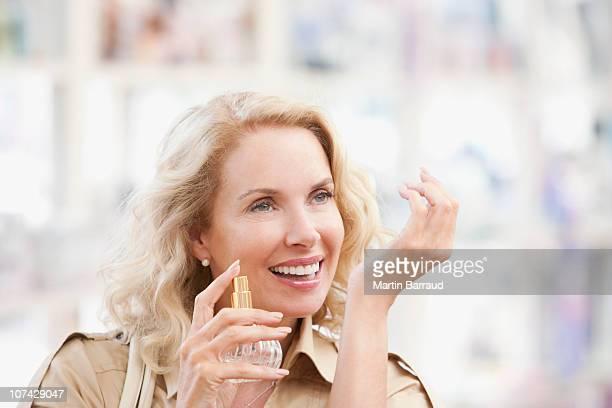 Mujer sonriente pruebas perfumes en la tienda