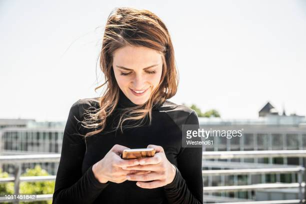 smiling woman text messaging on roof terrace - guardare in una direzione foto e immagini stock