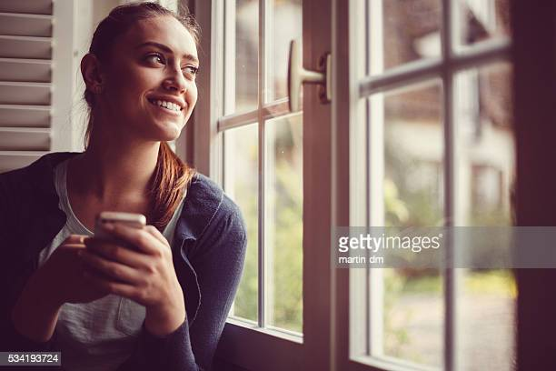 Smiling woman texting and looking through the window