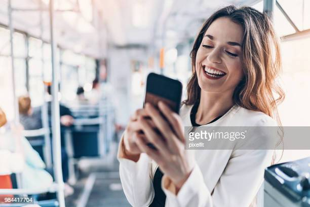 smiling woman texting in the bus - candid forum stock pictures, royalty-free photos & images