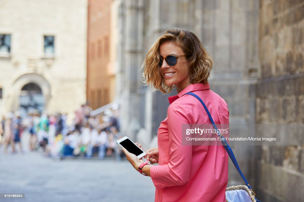 Smiling woman texting on cell phone on street in Barcelona : Stock Photo