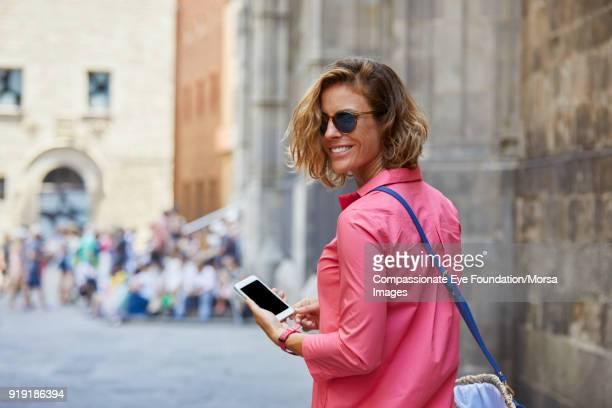 smiling woman texting on cell phone on street in barcelona - mulheres de idade mediana - fotografias e filmes do acervo