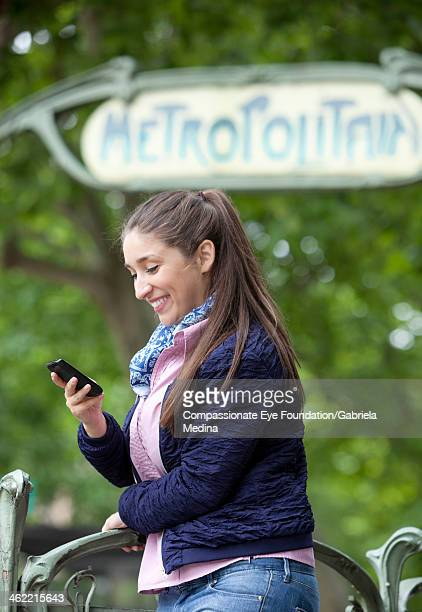 smiling woman texting on cell phone outdoors - cef do not delete stock pictures, royalty-free photos & images
