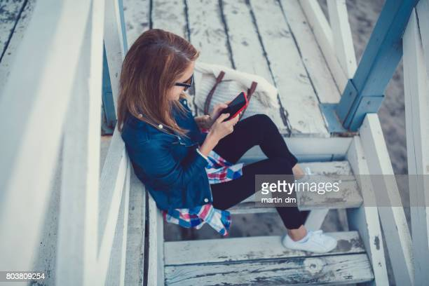 Smiling woman texting on the veranda