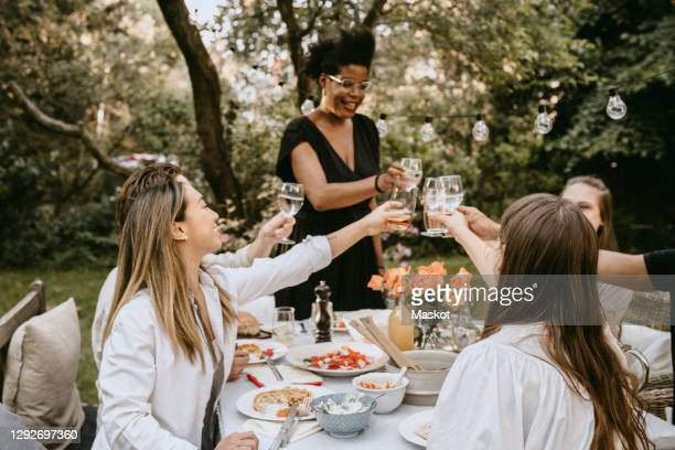smiling woman toasting drinks with friends over table during social gathering - garden party stock pictures, royalty-free photos & images
