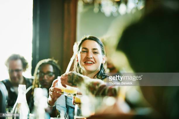Smiling woman toasting with friends while drinking in bar