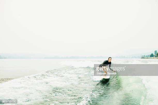 Smiling woman touching water while wakesurfing on lake