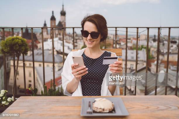 smiling woman traveling in europe and shopping online with credit card - making a reservation stock photos and pictures