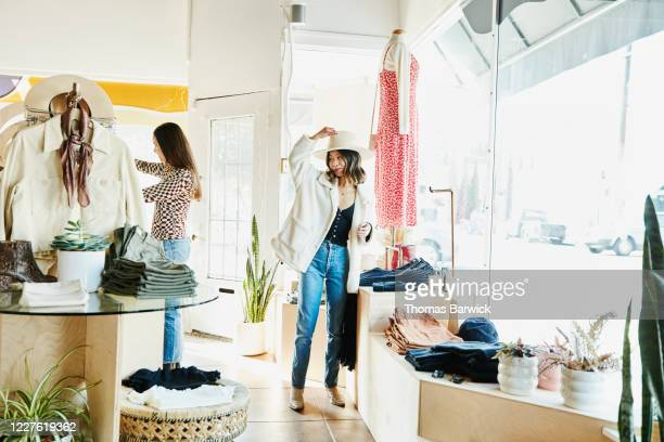 smiling woman trying on hat while shopping in boutique with friend - coat stock pictures, royalty-free photos & images