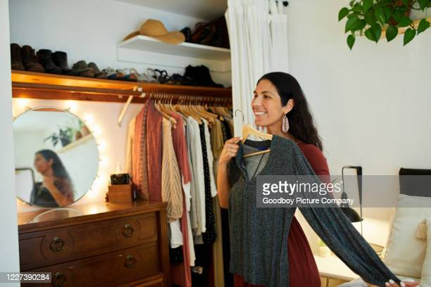smiling woman trying to choose a dress from her closet - trying on stock pictures, royalty-free photos & images