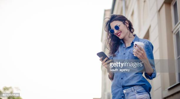 Smiling woman typing message on the mobile phone