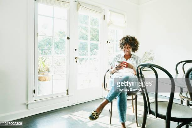 smiling woman typing on smart phone while sitting in dining room - afro amerikaanse etniciteit stockfoto's en -beelden
