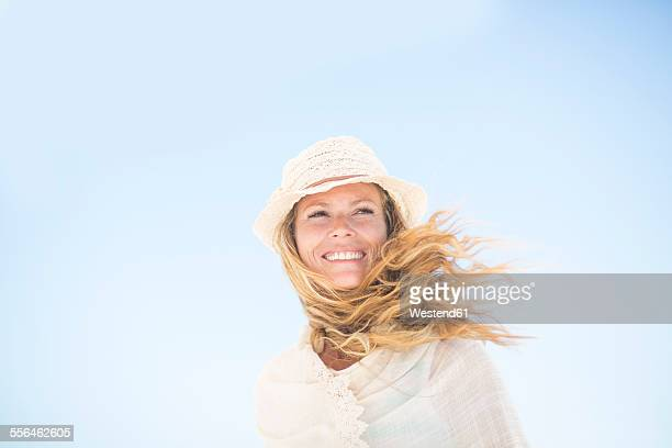 smiling woman under blue sky - blue hat stock pictures, royalty-free photos & images