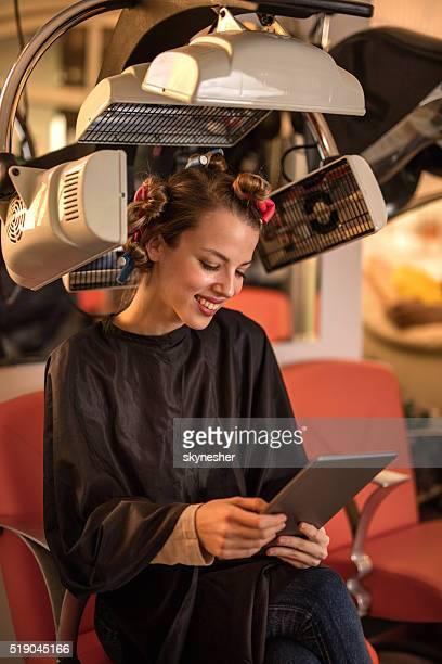 Femme souriante à l'aide de sèche-cheveux et de coiffeur tactile.