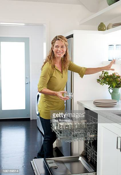 Smiling woman unloading the dishwasher