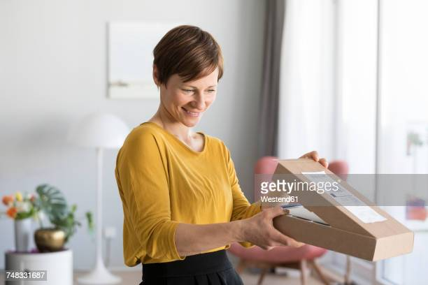 smiling woman unpacking parcel at home - recebendo - fotografias e filmes do acervo