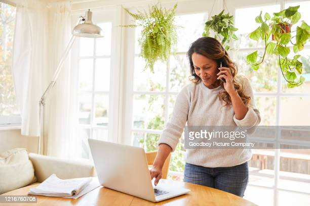 smiling woman using a cellphone and laptop while working at home - pacific islanders stock pictures, royalty-free photos & images
